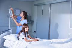 Nurse adjusting intravenous drip for girl patient in bed on hospital children's Stock Photos