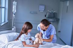 Nurse and girl patient playing with toy rabbit on hospital children's ward - stock photo