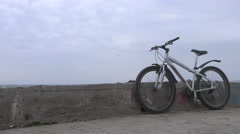 A lone bicycle stands on old high concrete pier during huge storm. Stock Footage