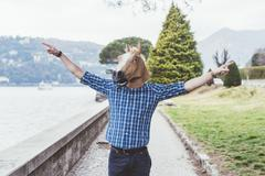 Portrait of man wearing horse mask with arms open, Lake Como, Italy - stock photo