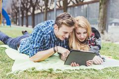 Young couple lying on picnic blanket looking at digital tablet,  Lake Como, - stock photo