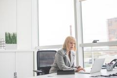 Mature businesswoman reading update on office laptop Stock Photos