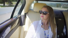 Pretty blonde woman enjoying trip on backseat of expensive auto, tourism Stock Footage