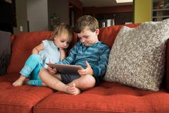 Siblings using digital tablet on sofa Stock Photos