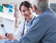 Doctor sharing health information on digital tablet with patient in clinic - stock photo