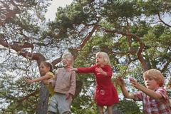 Small group of young friends playing outdoors, watching bubbles in air - stock photo