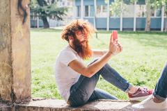 Young male hipster with red hair and beard photographing friend on smartphone in - stock photo