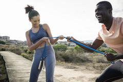 Couple tugging on skipping rope smiling Stock Photos