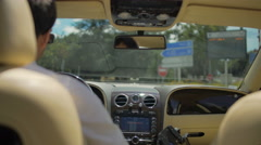 View on road from backseat of luxury vehicle, business driver behind the wheel Stock Footage