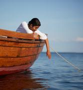 Woman dangling arm over boat - stock photo