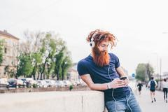 Young male hipster with red hair and beard choosing headphone music in city - stock photo