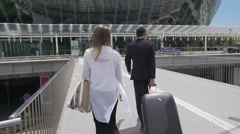 Glamorous female and bodyguard with her luggage walking at the airport, tourism Stock Footage