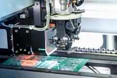 Robot placing components onto circuit board in circuit board assembly factory - stock photo