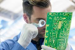 Worker inspecting circuit boards in circuit board assembly factory Stock Photos