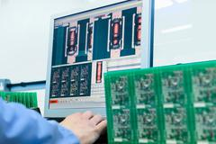 Worker testing circuit boards in circuit board assembly factory, close up Stock Photos