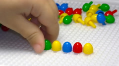 Close up of child's hand playing with mosaic Stock Footage