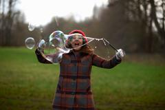 Woman in park using bubble wand to make bubbles Stock Photos