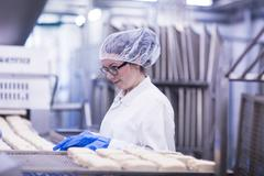 Woman working in food production factory - stock photo