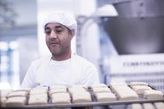 Man working in food production factory carrying tray - stock photo