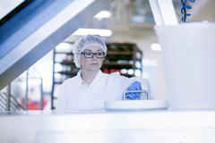 Factory worker wearing hair net in food production factory - stock photo