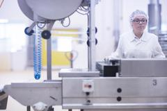 Factory worker operating food production machinery Stock Photos