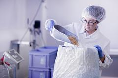 Factory worker scooping food into sack - stock photo