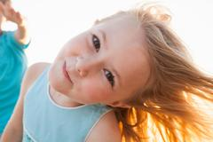 Portrait of girl, head cocked, looking at camera smiling - stock photo