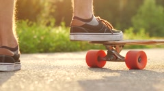 Stylish middle-aged man starts to move on longboard in the park. Slow motion Stock Footage