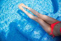 Overhead waist down view of young woman wearing bikini bottoms relaxing on Stock Photos