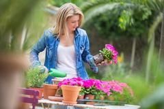 Young woman tending pink flower pot plant at garden table - stock photo