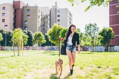 Young woman walking pit bull terrier in urban park - stock photo