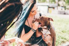 Young women with dyed blue hair playing with pit bull terrier in urban park - stock photo