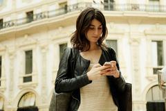 Woman reading smartphone text in Galleria Vittorio Emanuele II, Milan, Italy - stock photo