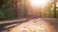 Stylish young man riding on longboard in the park at sunset. Slow motion Stock Footage