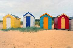 Front view of a row four multi-coloured beach huts, Southwold, Suffolk, UK - stock photo