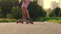 Stylish middle-aged man riding on longboard in the park at sunset. Slow motion Stock Footage