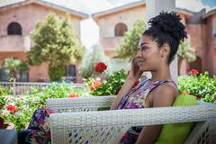 Young woman relaxing on apartment patio talking on smartphone, Costa Rei, Stock Photos
