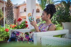 Young woman relaxing on apartment patio drinking cocktail, Costa Rei, Sardinia, Stock Photos