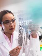 Scientist viewing a DNA profile experiment in a laboratory - stock photo