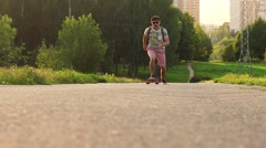 Stylish middle-aged man riding on longboard in the park. Slow motion Stock Footage