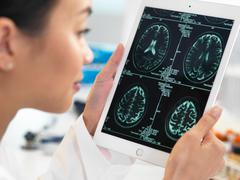 Doctor viewing CT scan result of brain on digital tablet for abnormalities Stock Photos