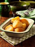 Golden roast potatoes in vintage dish, wooden table Stock Photos