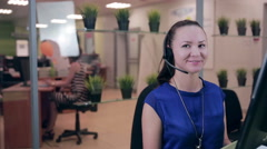 Frendly woman talking on the headset in a bright clean office, call center Stock Footage