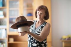 Woman holding up felt hat Stock Photos