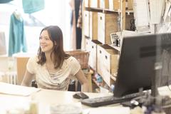 Young female shop assistant using wheelchair behind shop checkout - stock photo