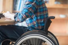 Young man using wheelchair connecting control panel and transformer at kitchen - stock photo
