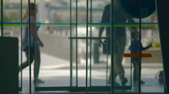 Automatic doors in shopping center, people entering and exiting building Stock Footage
