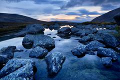 Calm water and boulders at Chasnayok river, Khibiny mountains, Kola Peninsula, - stock photo