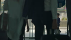 Female and male travelers walking out through airport automatic opening doors Stock Footage