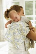 Mother burping baby son whilst carrying him on her shoulder Stock Photos